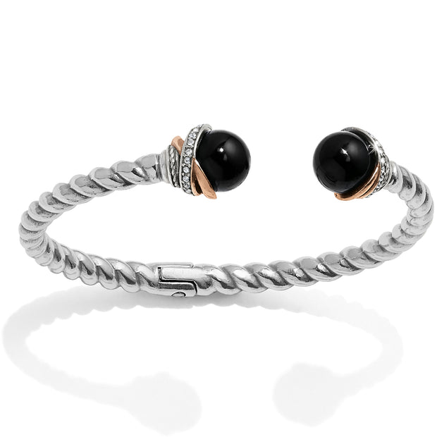 Brighton Jewelry Neptune's Rings Black Agate Open Hinged Bangle. Symbolizing spiritual contentment, semi-precious black agate spheres cap the end of this rope bangle, finished with our Neptune's Rings motif including rose gold plate.
