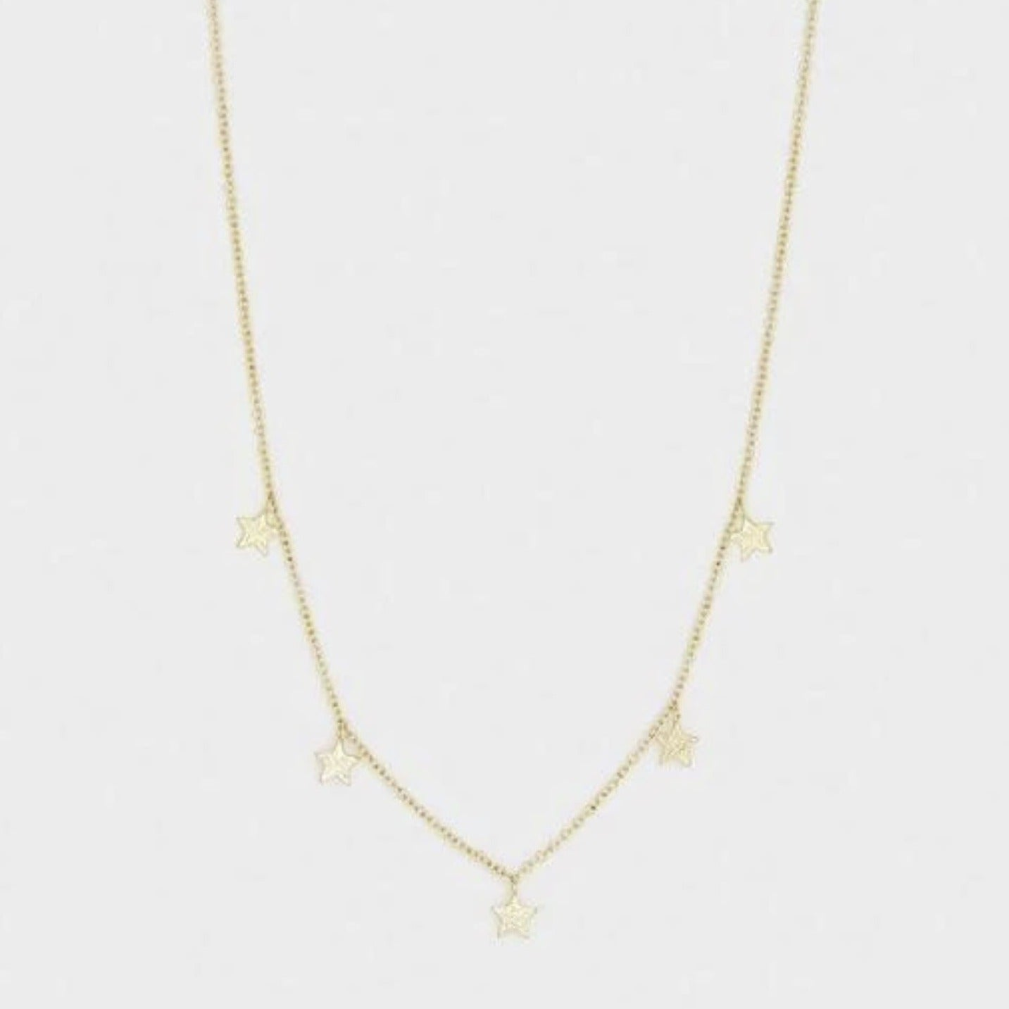 "Inspired by our best-selling Super Star collection. This delicate gold star necklace adds a celestial shine to any outfit. Adjustable Chain extends out to 16"" Charms are approximately 3/16"" in diameter Spring ring closure with silicone slide bead Available in 18k gold plated brass."