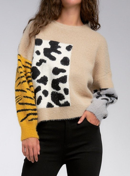 Set Out In The Wild in this mixed print sweater. Combining cheetah print, comfy texture, and colorblock, this statement sweater is a must-have. Turn heads this season with this unique style that's effortless to style up or down. Sweater has a boxy fit but is cropped.