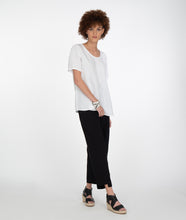 Load image into Gallery viewer, model in a white tshirt and black pants with an uneven hem at the ankles. paired with black sandles, standing in front of a white background
