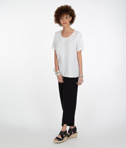 model in a white tshirt and black pants with an uneven hem at the ankles. paired with black sandles, standing in front of a white background