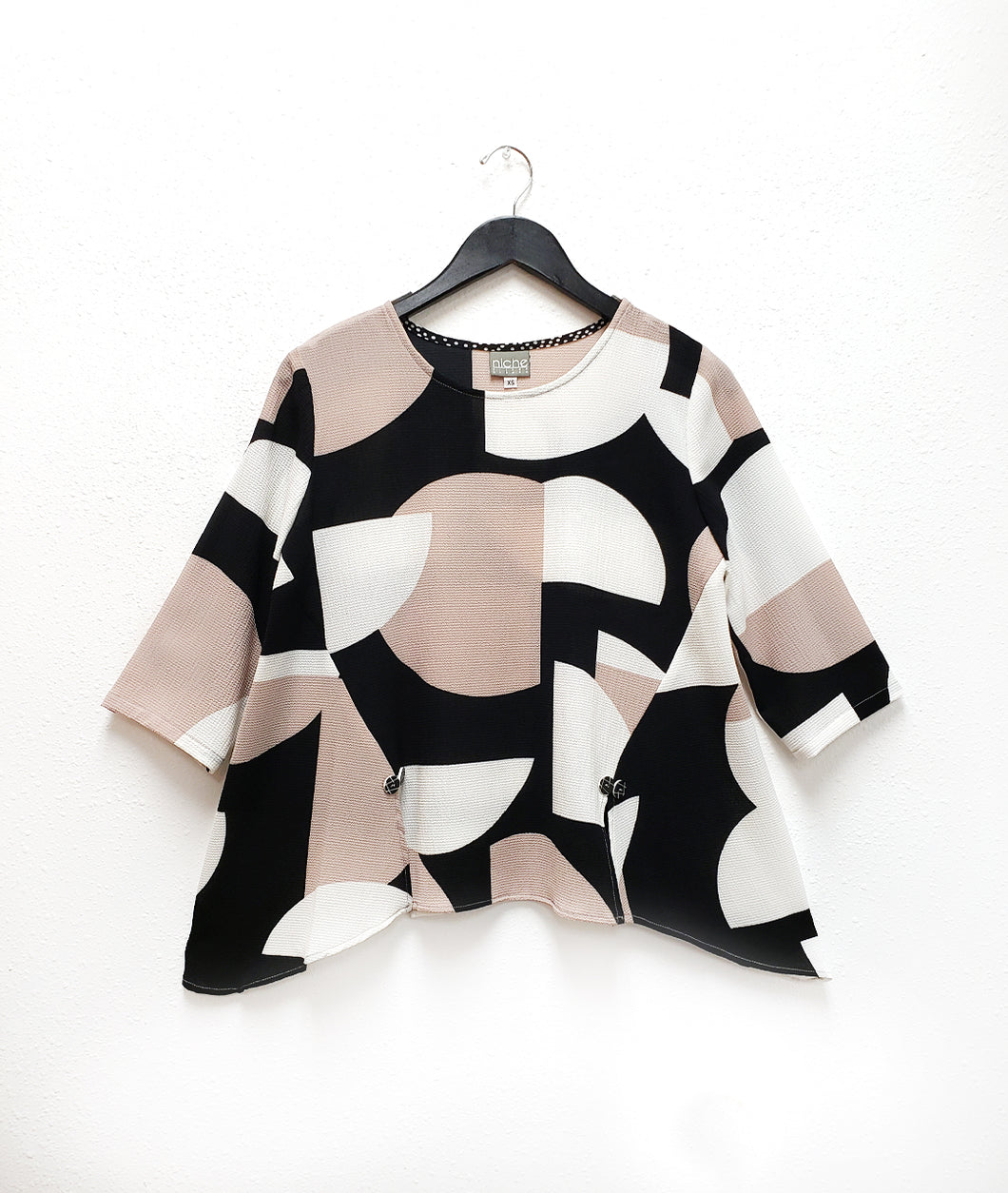 black, white and taupe pull over top with princess seams ending in a split at the bottom hem with a twin button detail.