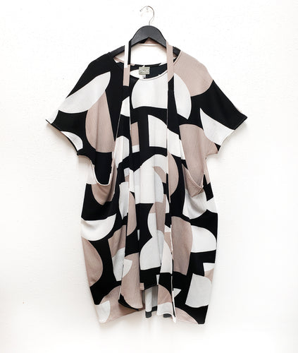 black, white and taupe tunic with two extended side panels attached with a strap worn around the neck, halter style