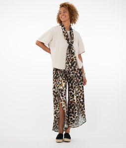 model in a bone colored top with animal print pants and scarf, in front of a white background