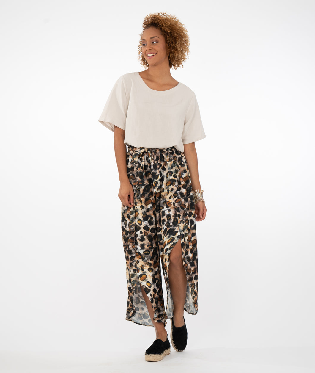 model in a tan top with wide open leg animal print pants