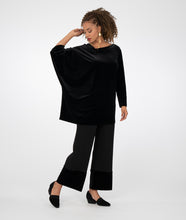 Load image into Gallery viewer, model in a black asymmetrical tunic worn with a wide leg black pant with a contrasting fabric at the bottom hems