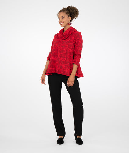 model in black straight leg pants with a red pullover top with a cowl top, in front of a white background