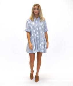 model in a blue and white stripe and dot print shirt dress with a gathered skirt