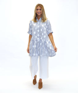 model in a blue and white stripe and dot print shirt dress with a gathered skirt worn over white pants
