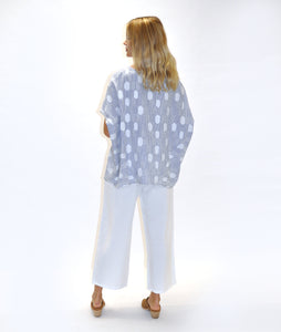 model in white pants and a pullover blouse in a blue and white stripe prin, with white dots, in front of a white background