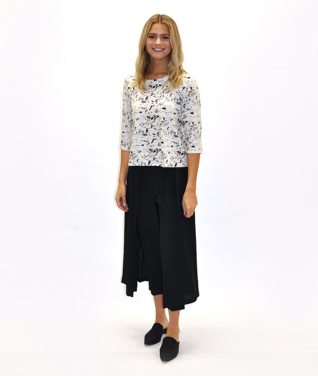 model in a black pant with a terrazzo print tee, in front of a white background