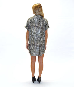 model in a leopard print boxy dress with a v neck and cuffs at the sleeves, in front of a white background