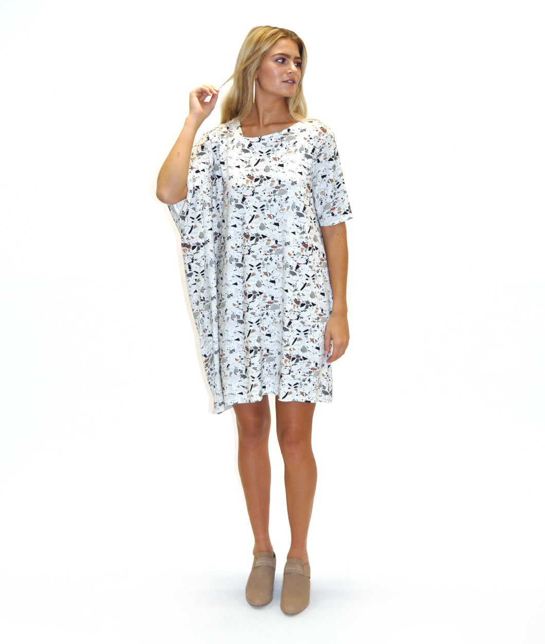 model in a terrazzo print asymmetrical tunic in front of a white background