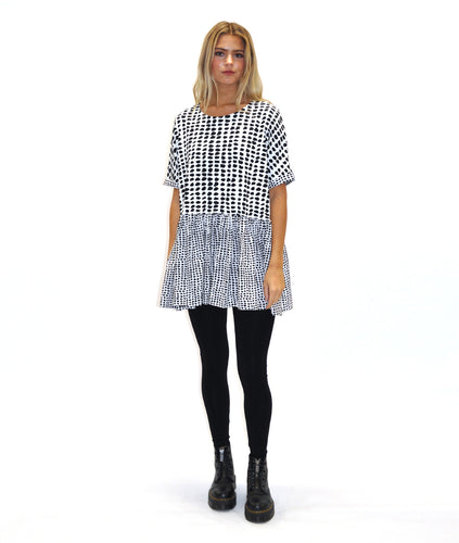 model in a black and white dot print top, with a smaller print pattern on the sleeve cuffs and skirt