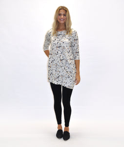 model in a terrazzo print tunic with an asymmetrical drape at the side
