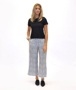 model in a black tshirt with a black and white polkadot print wide leg pant, in front of a white background