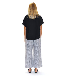 model in a black and white polkadot print pant, worn with a black pullover top with a vneck and cuffed sleeves
