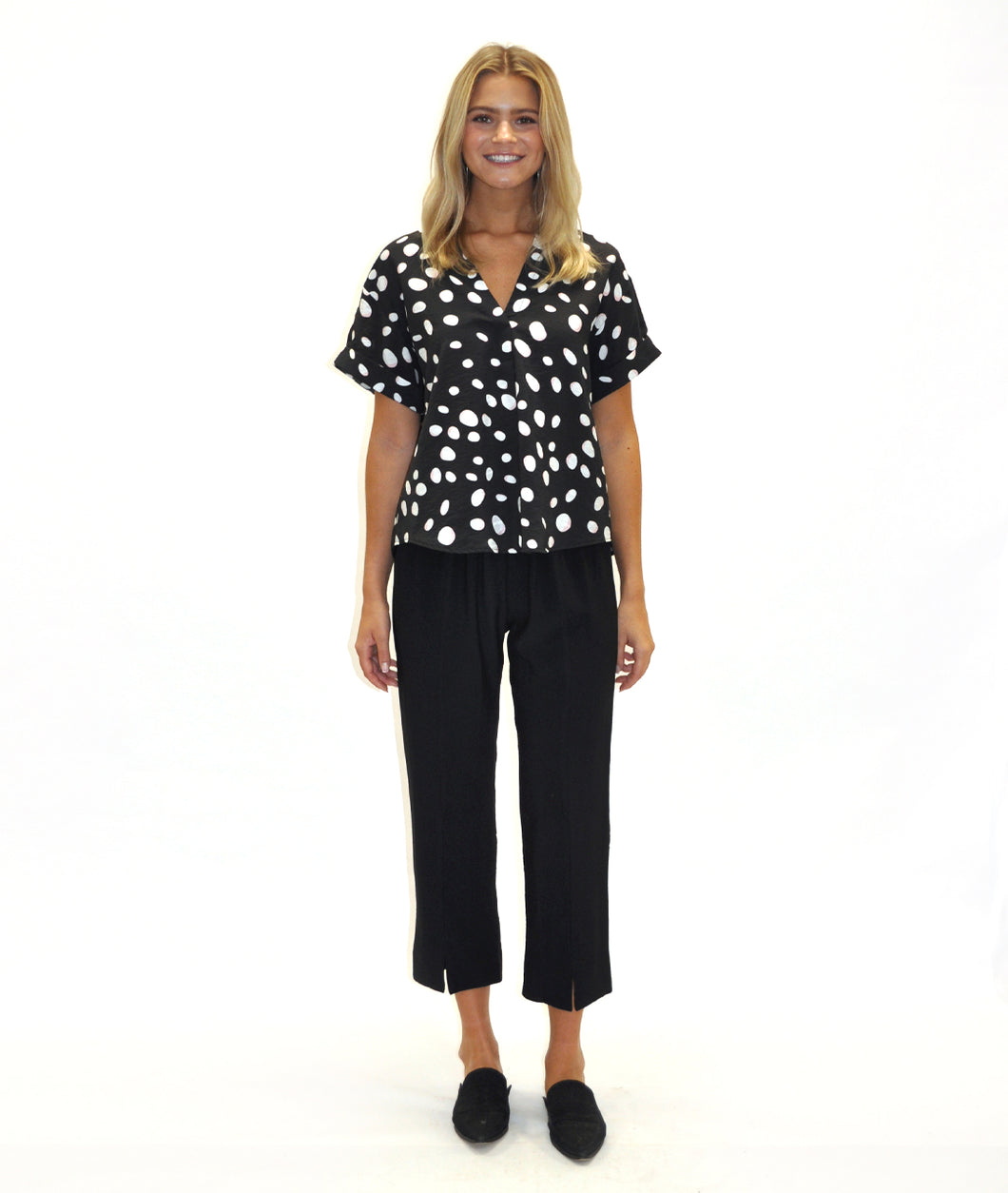 model in a black, polkadot print top with a short black pant, in front of a white background