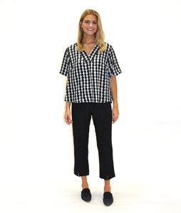 model in black pants with a black and white print top with a vneck and short sleeves, in front of a white background