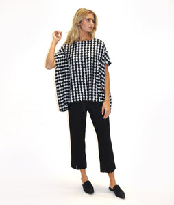 model in black pants with a short sleeve black and white poncho style top, in front of a white background