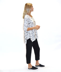 model in a terrazzo print tee with a hankerchief hemline, worn with black pants, in front of a white background