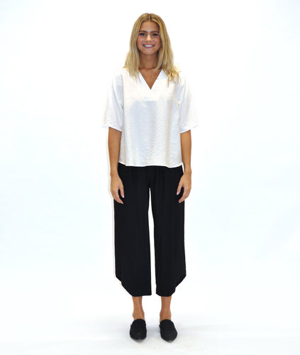 model in a black pant with an angled hem, worn with a white vneck top with short sleeves