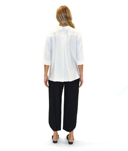 model in a white button down blouse with black pants, in front of a white background