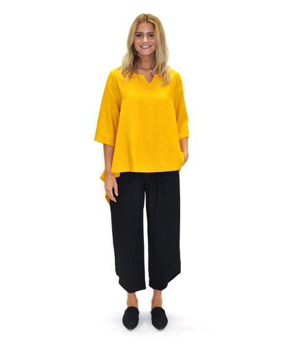 model in a yellow top with a black pant with an angled hem