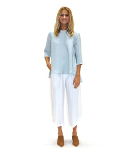 model in a light blue flowy top with white pants
