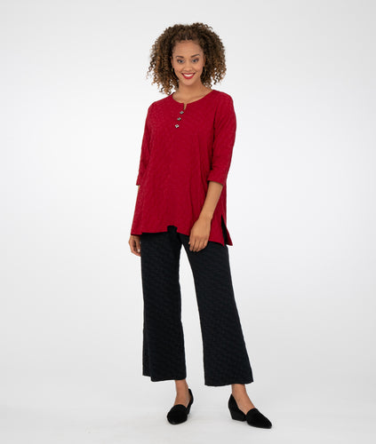 model in a red blouse with a wide leg black pant