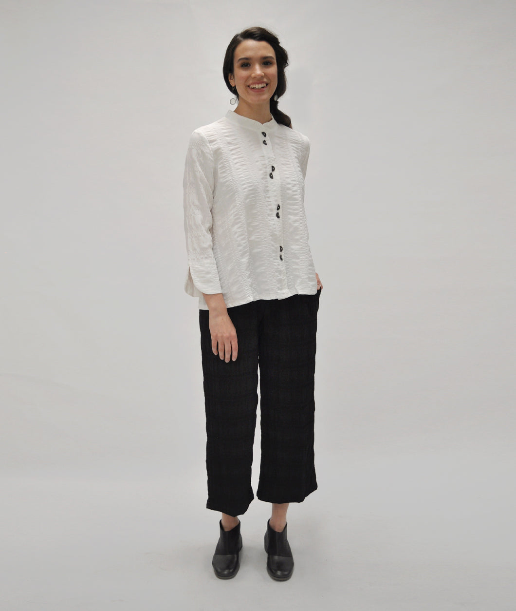model in black wide leg pants with a white button up blouse with twin half circle buttons down the front and a short standing collar. sleeves have rounded cuffs with a split at each elbow