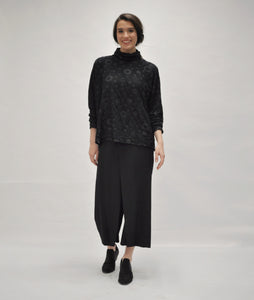 model in a black straight leg pant with a black top. top is black with a circle dot print and a wrinkled texture. top has a cowl neckline, long sleeves and a boxy body