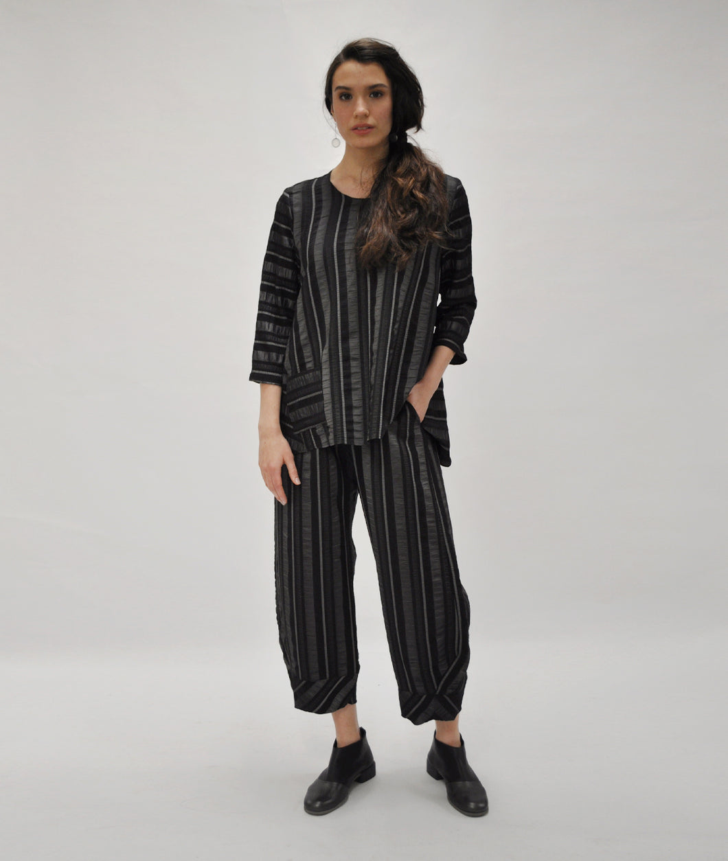 model in a black and silver striped pant with a matching top with a wide body and single pocket at the hip