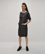 Load image into Gallery viewer, model in a silver and black striped shift dress with princess seams and squared pockets at the hips