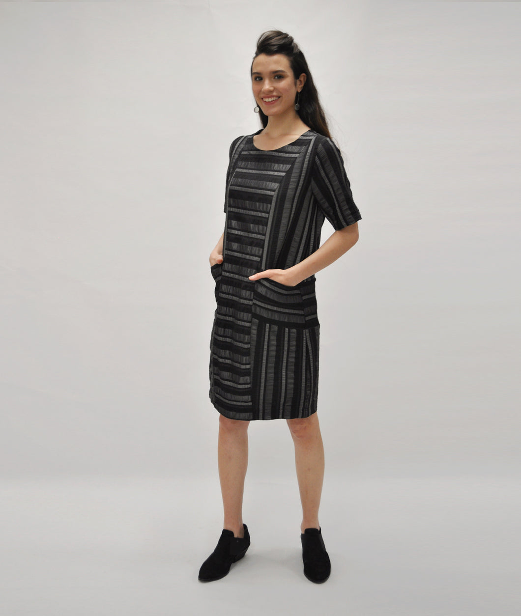 model in a silver and black striped shift dress with princess seams and squared pockets at the hips
