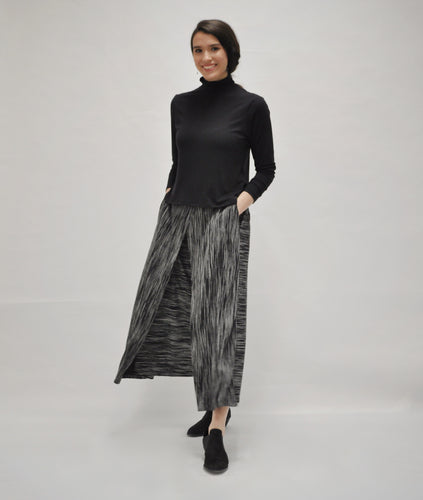 model in a black turtleneck with a black and grey striped wide leg pant