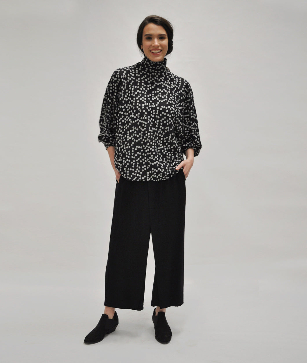 model in a wide leg black pant with a black and grey boxy polkadot top with a cowl neck