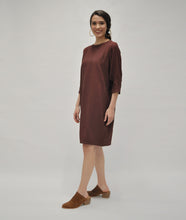 Load image into Gallery viewer, model in a burgundy shift dress with a pleating detail at the sleeves
