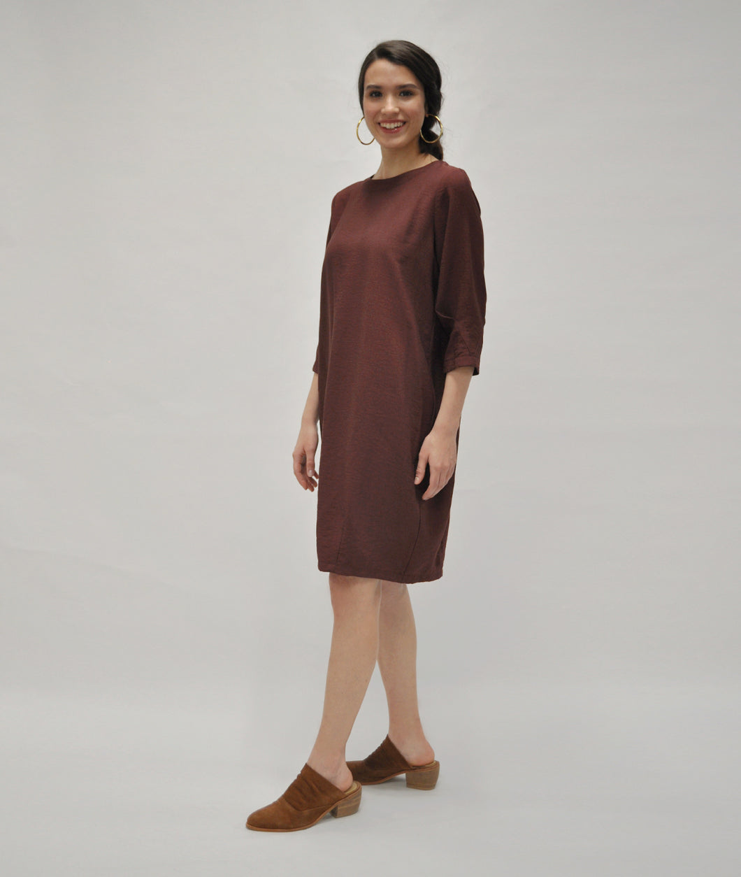 model in a burgundy shift dress with a pleating detail at the sleeves