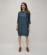Load image into Gallery viewer, model in a teal shift dress with a pleating detail at the sleeves