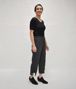 model in a black top worn with a black and white dot print pant with a center front seam and a split detail with a button at each ankle