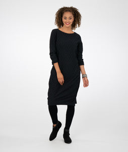 model in a textured black dress with long sleeves