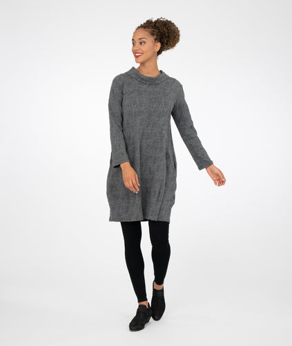 model in black leggings with a gray tunic with a standing, fold over collar with a split in the back, standing in front of a white background