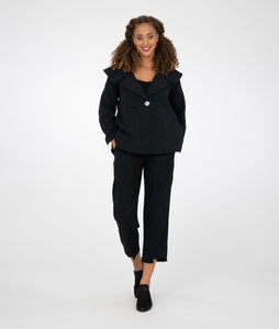 model in a black textured jacket with a wide collar and matching black pants
