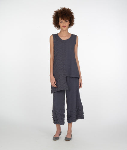 model in a grey textured pant with contrasted hem, worn with a matching sleeveless top with an asymmetrical hem