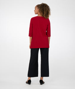 model in black pants with a red top with an asymmetrical hem and button detail at the neck