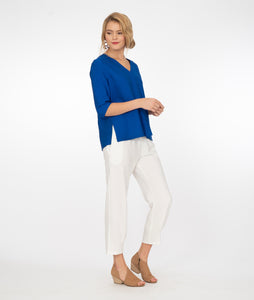 model in a v neck electic blue top with white pants, in front of a white background