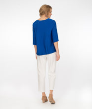 Load image into Gallery viewer, model in a v neck electic blue top with white pants, in front of a white background