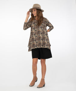 model in an animal print shirt with black shorts, a hat and boots in front of a white background