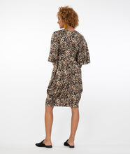 Load image into Gallery viewer, Model in an animal print kaftan style dress in front of a white background